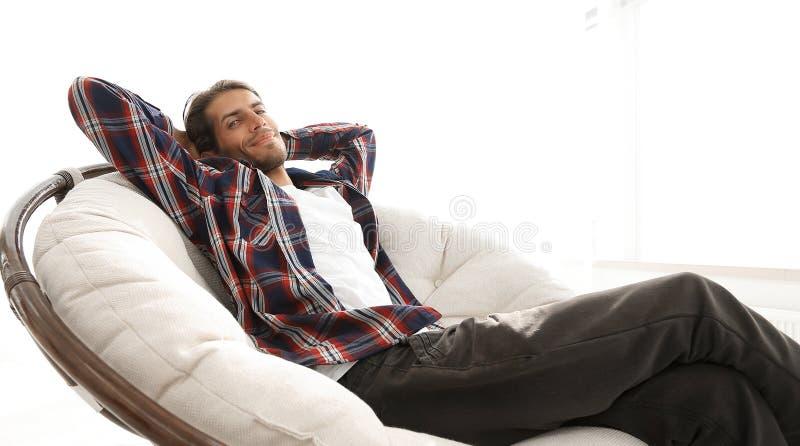 De moderne kerel rust zitting als grote comfortabele voorzitter Zachte nadruk stock foto's