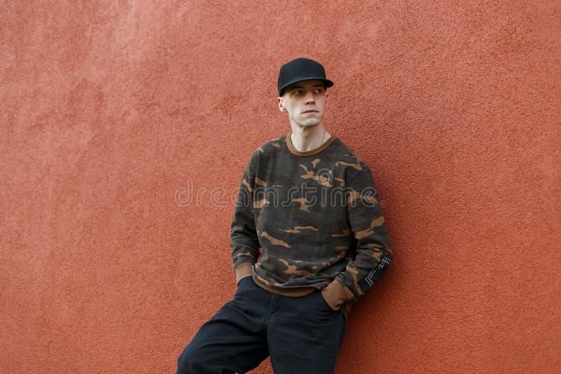 De moderne knappe mens in een modieus zwart GLB in een modieus camouflageoverhemd in in jeans ontspant dichtbij een uitstekende m stock afbeelding