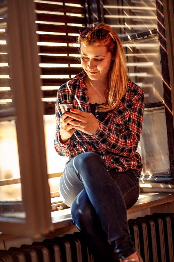 De moderne levensstijl van de mensenstad stedelijk meisje die een cellphone houden en stock foto