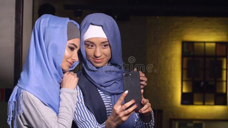 De moderne Moslimvrouwen nemen beelden op een mobiele telefoon Meisjes in en hijabs die spreken glimlachen stock afbeelding