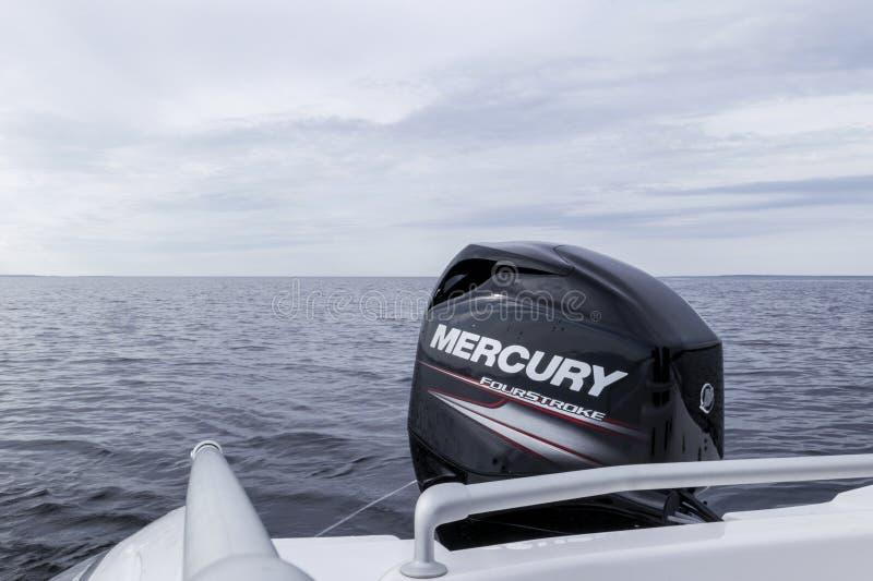 De moderne nieuwe boot van de visserijsport met een gloednieuwe buitenboordmotor van Mercury FourStroke op het meer stock afbeelding