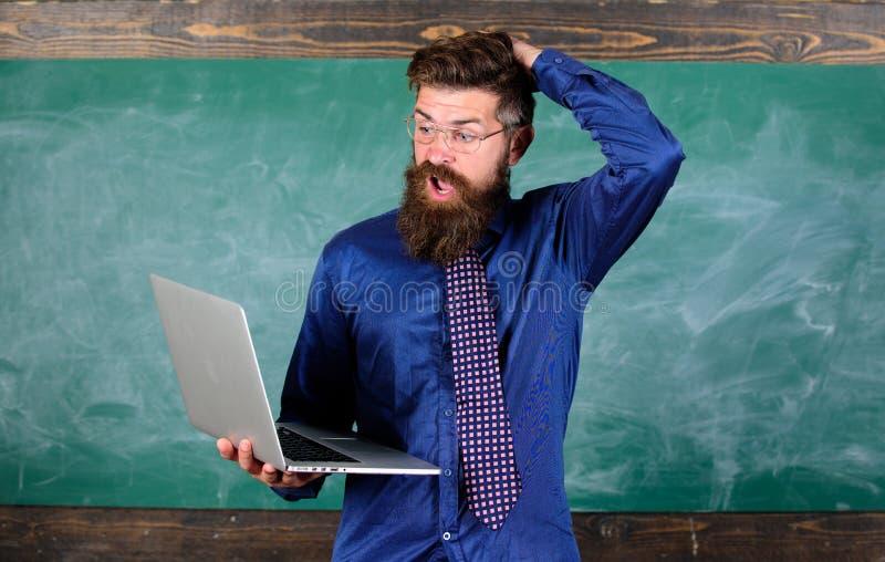 De moderne technologie blaast zijn mening Modern onderwijsprogramma De Hipsterleraar met laptop wordt verrast die gaat ongeveer g stock foto's