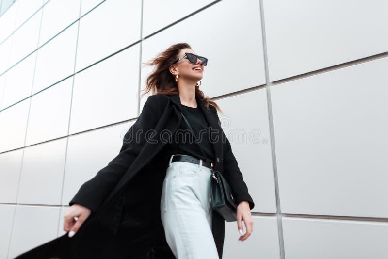 De moderne vrolijke jonge hipstervrouw met een positieve glimlach in zonnebril in zwarte in kleren reist rond de stad royalty-vrije stock fotografie