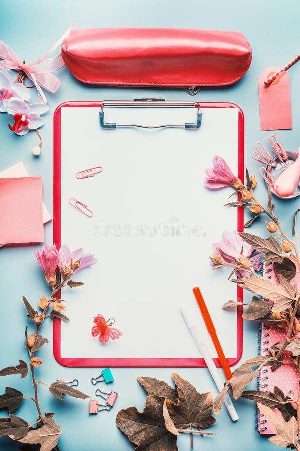 De moderne vrouwelijke Desktop van het huisbureau in rozerode kleur met bloemen, toebehoren en leeg klembord op blauwe achtergron royalty-vrije stock foto