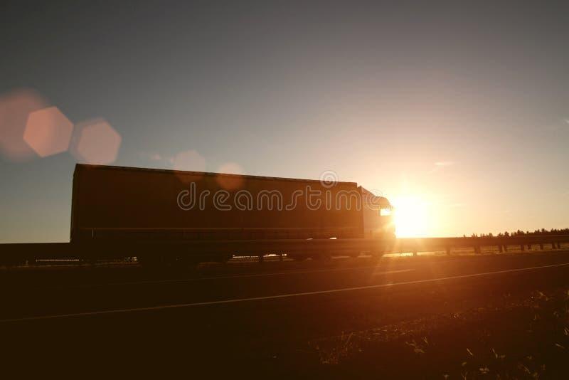 De moderne wagenvrachtwagen vervoerden lading tegen de achtergrond van een zonsondergang Het concept vrachtwagenchauffeurs op het royalty-vrije stock fotografie