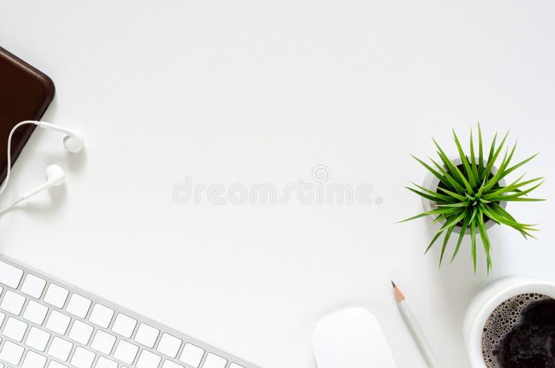 De moderne werkplaats met draadloze toetsenbord en muis, een kop van koffie, smartphone met oortelefoons, het potlood en Tillands royalty-vrije stock foto