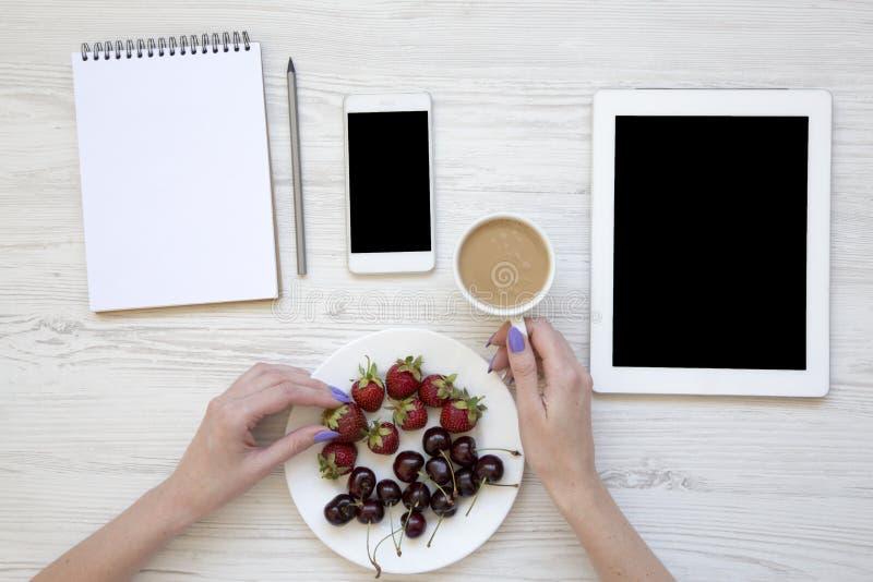 De moderne werkruimte met vrouwelijke handen, het notitieboekje, het potlood, smartphone, de tablet, de bessen en de koffie vorme royalty-vrije stock fotografie