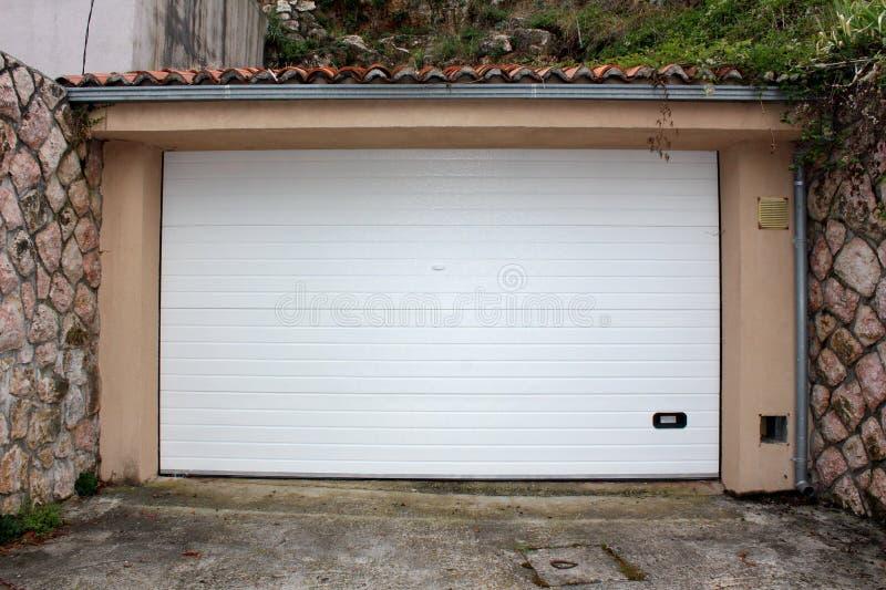 De moderne witte deuren van de rollupgarage met klein handvat voor het hand openen zetten op vernieuwde die garagemuur met tradit stock foto's