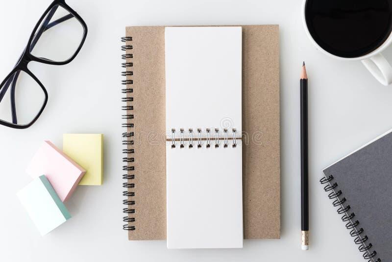 De moderne witte lijst van de bureaudesktop met notitieboekje, nota, een kop van stock foto's