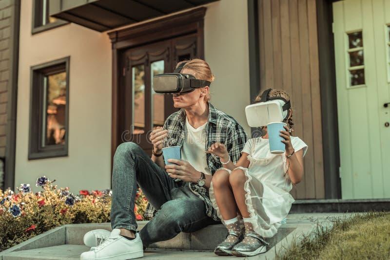 De moderne zitting van de blondevader op de portiek met zijn dochter royalty-vrije stock fotografie