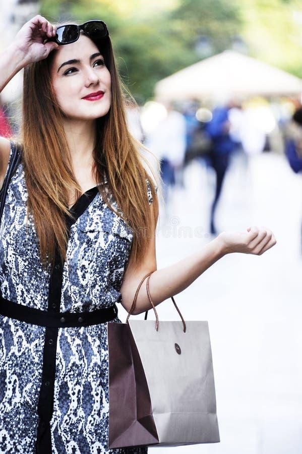 De modieuze, aardige en aantrekkelijke jonge vrouw winkelt in de stad met document zakken in haar hand stock afbeelding