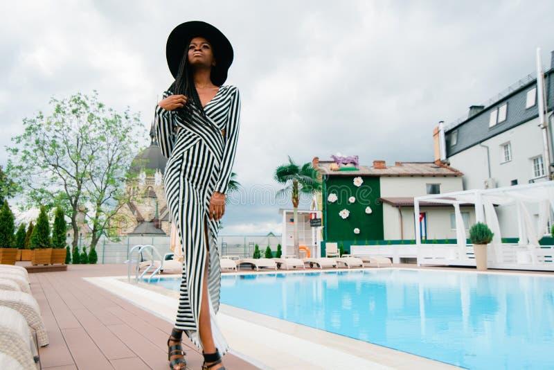 De modieuze Afrikaanse dame in lange kleding in strepen en zwarte hoed loopt dichtbij de pool pf het luxehotel stock afbeeldingen