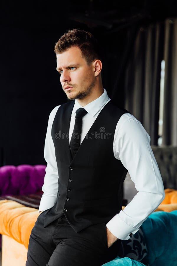 De modieuze atletische mens in een bedrijfskostuumvest zit als turkooise bankvoorzitter, een ernstige blik stock foto's