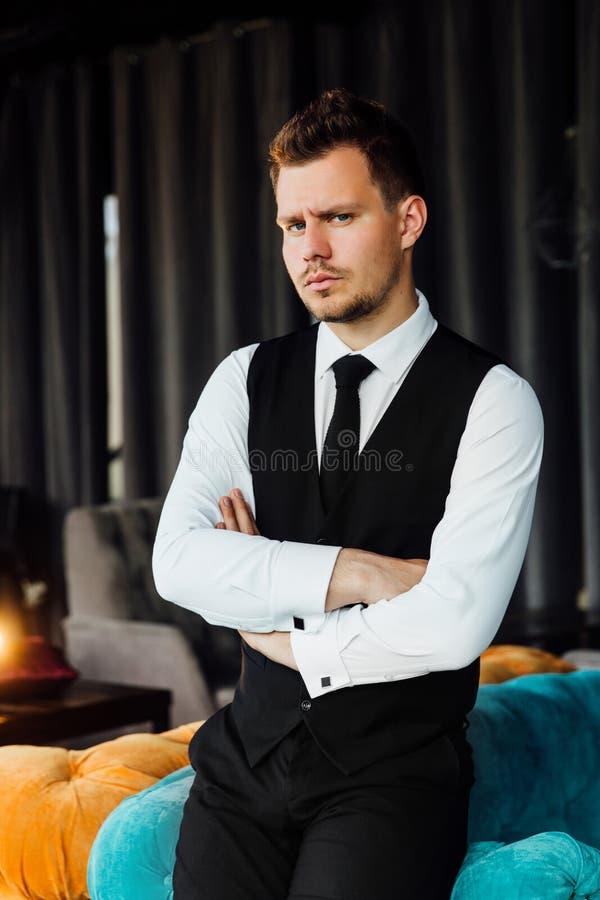 De modieuze atletische mens in een bedrijfskostuumvest zit als turkooise bankvoorzitter, een ernstige blik royalty-vrije stock foto's