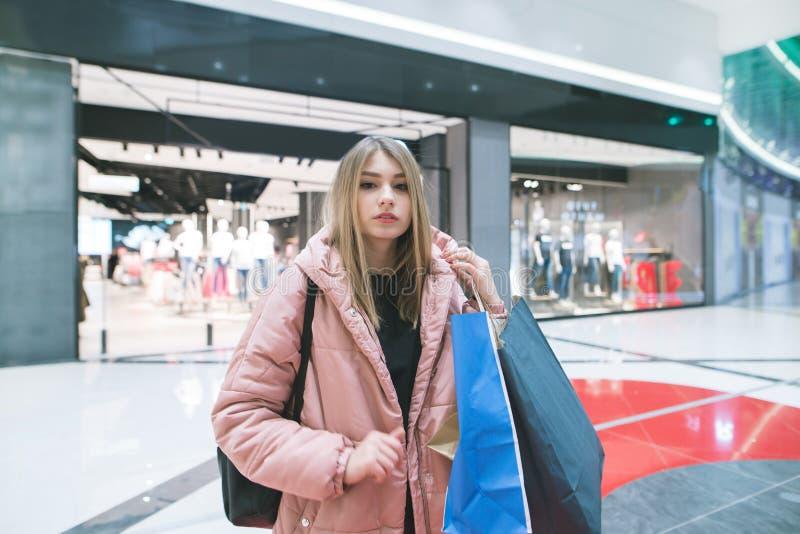 De modieuze blondevrouw met het winkelen in haar handen bevindt zich op de achtergrond van een kledingsopslag Het winkelen concep stock afbeeldingen
