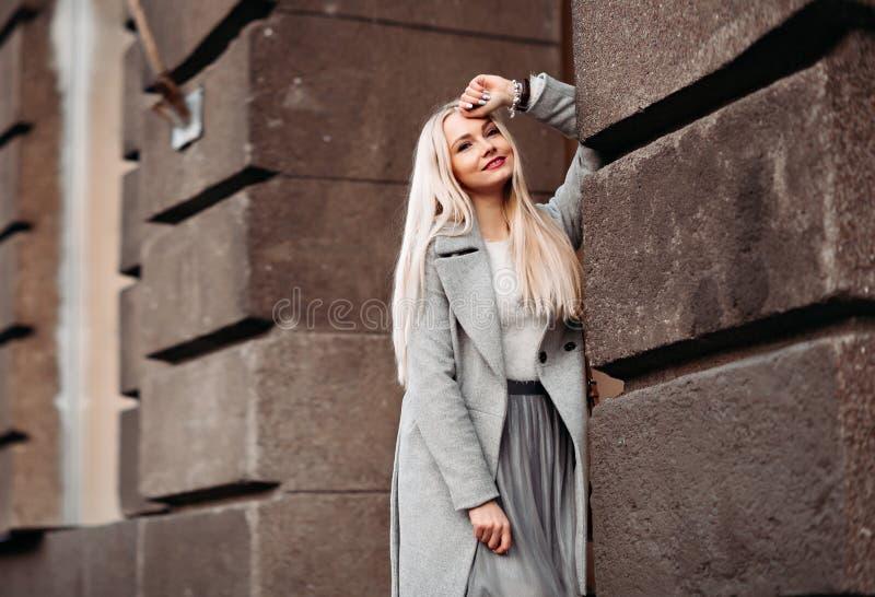 De modieuze blondevrouw in de romantische lente kijkt dromend stock afbeelding