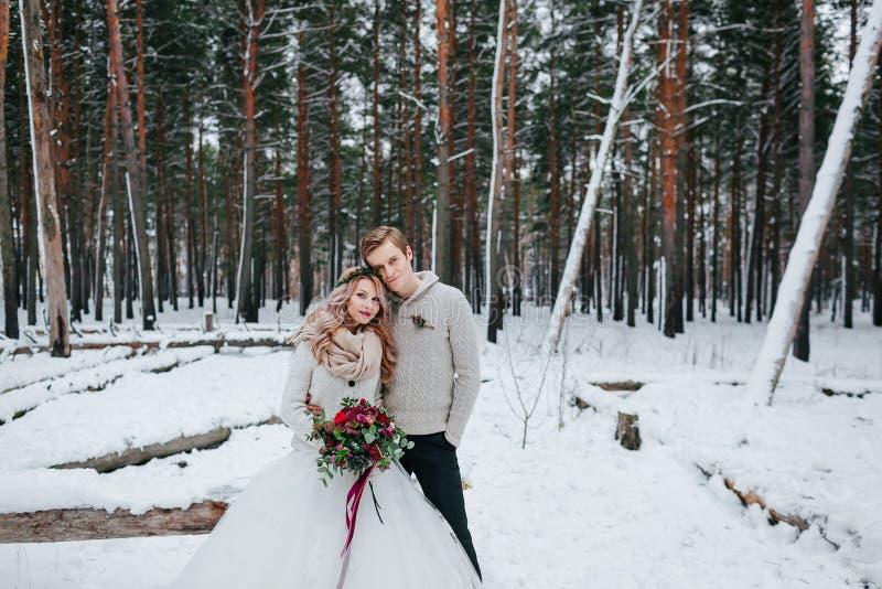 De modieuze bruid en de bruidegom met een boeket stellen op achtergrond van het sneeuw bos de Winterhuwelijk stock foto