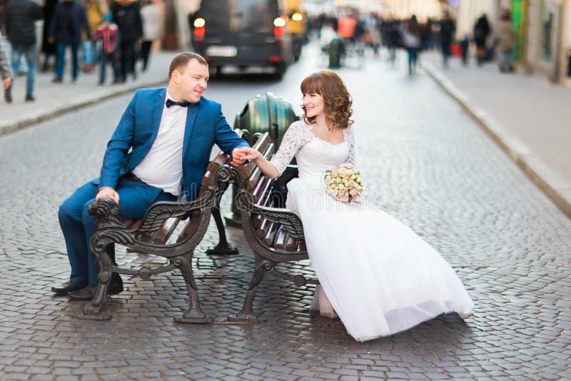 De modieuze bruid van het huwelijkspaar in witte kleding en elegante bruidegomzitting op de handen van een bankholding stock foto