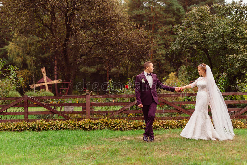De modieuze bruidegom in wijnkostuum houdt bride& x27; s hand terwijl het lopen alon royalty-vrije stock afbeeldingen