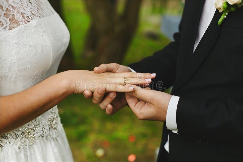 De modieuze bruidegom zet op de verlovingsring op de vinger van zijn mooie bruid bij de huwelijksceremonie Sterk mannetje stock afbeelding