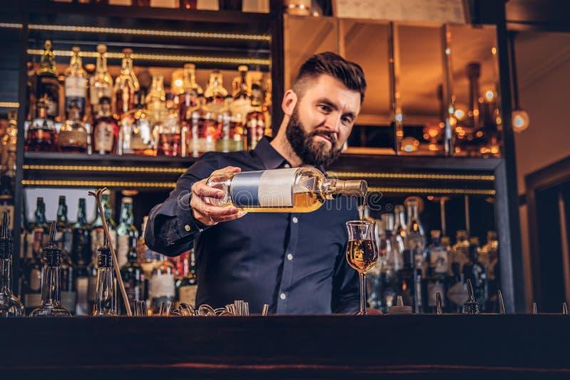 De modieuze brutale barman in een zwart overhemd maakt een cocktail bij bar tegen zich achtergrond verzetten royalty-vrije stock afbeeldingen