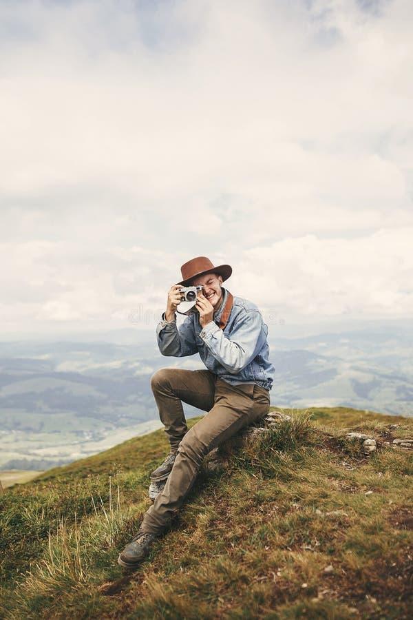 De modieuze camera van de de holdingsfoto van de hipsterreiziger en het nemen van beeld bovenop heuvels op achtergrond van mistig stock fotografie