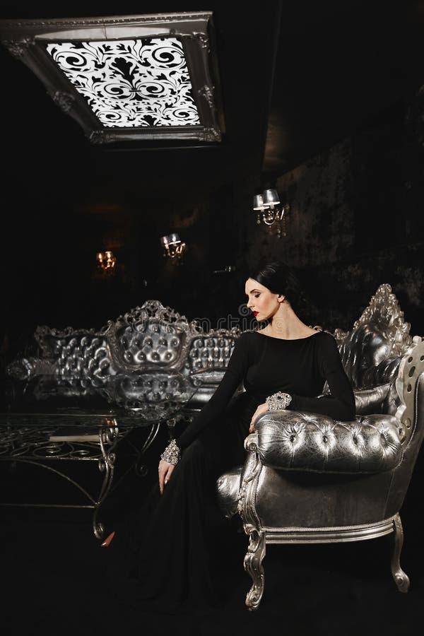De modieuze en sexy donkerbruine modelvrouw met perfect lichaam en met rode lippen in zwarte avondjurk met zit op royalty-vrije stock afbeelding