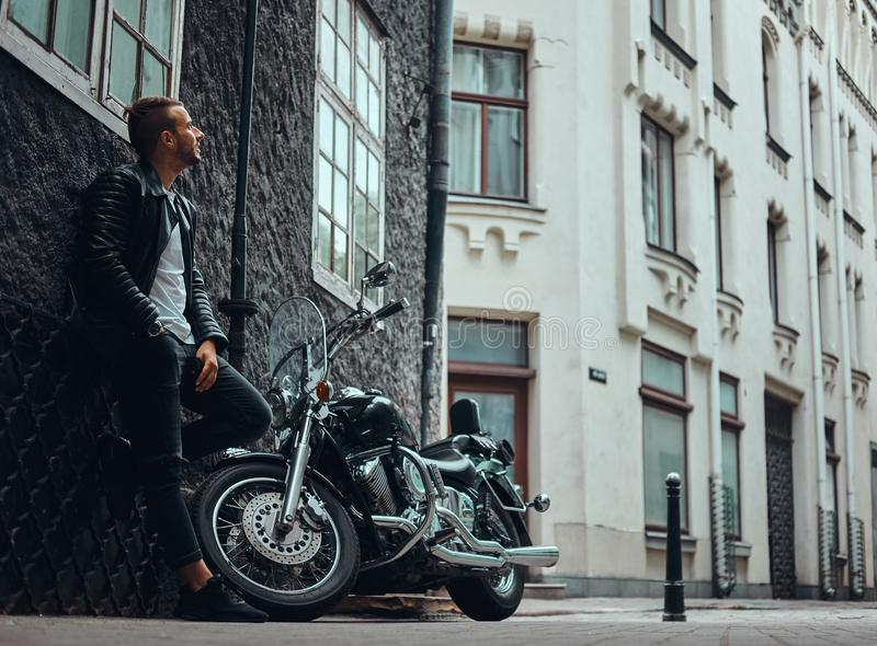 De modieuze fietser kleedde zich in een zwart leerjasje en jeans die op een muur dichtbij zijn retro motorfiets op oud Europa leu royalty-vrije stock afbeeldingen