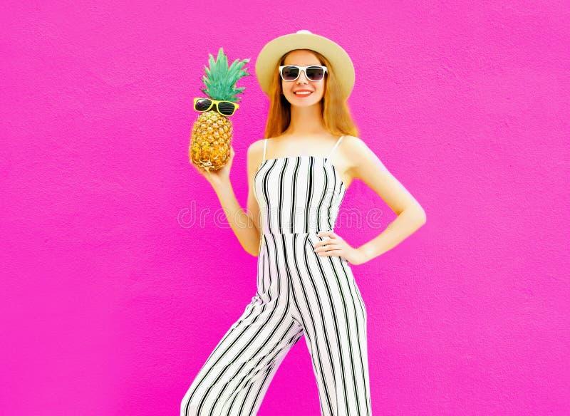De modieuze gelukkige het glimlachen ananas die van de vrouwenholding gestreepte jumpsuit, de zomer om strohoed dragen op kleurri royalty-vrije stock fotografie