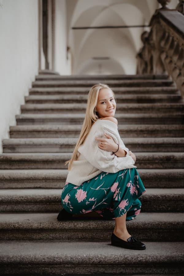 De modieuze gelukkige zitting van de blonde jonge vrouw op de treden royalty-vrije stock foto