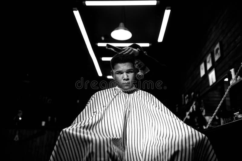 De modieuze herenkapper De manierkapper maakt een modieus kapsel voor een zwart-haired mensenzitting in de leunstoel stock fotografie