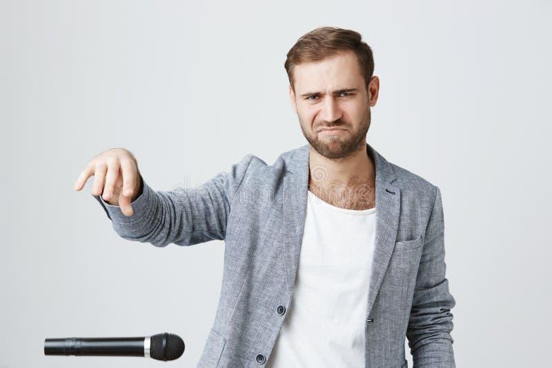 De modieuze hipsterkerel met baard draagt in kleren, treft voor muziekoverleg voorbereidingen, repeteert, gebruikt microfoon en w royalty-vrije stock afbeeldingen