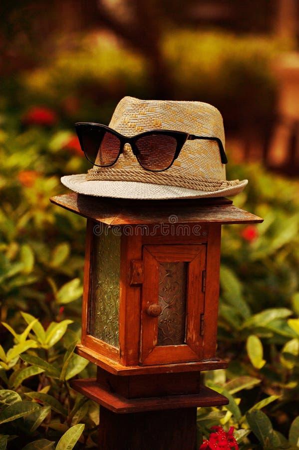 De modieuze hoed, mof, napper met zonnebril, bril bevindt zich op de lamp met warme tonen in de zomertijden stock foto