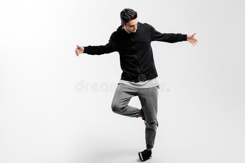 De modieuze jonge danser die een zwart sweatshirt en een grijze broek dragen is dansende heup -heup-poh royalty-vrije stock fotografie