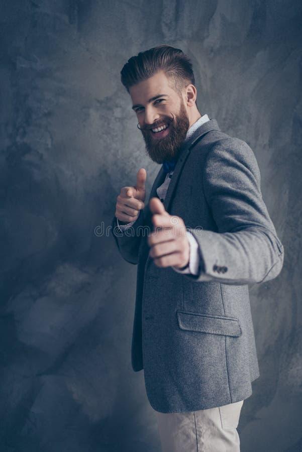 De modieuze jonge gebaarde mens in een kostuum bevindt zich op een grijze achtergrond stock foto