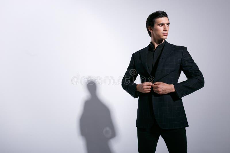 De modieuze jonge knappe mens in een elegant kostuum, schikte zijn die jasje in controleurs, op witte achtergrond worden geïsolee royalty-vrije stock afbeelding