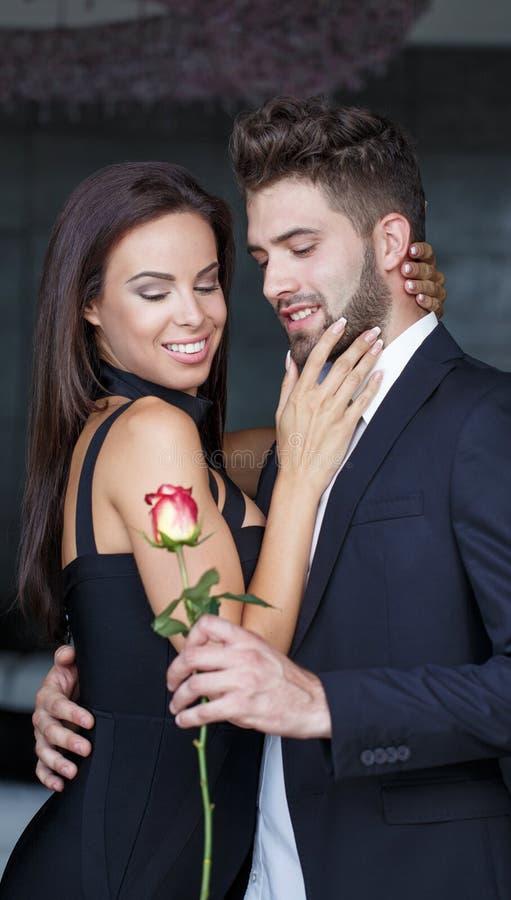 De modieuze jonge man geeft rood toenam tot vrouw bij valentijnskaartendag stock foto's