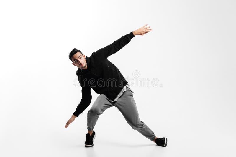 De modieuze jonge mens is dansende heup -heup-poh op een witte achtergrond Hij buigt zijn knieën en spreidt zijn wapens aan de ka royalty-vrije stock foto's
