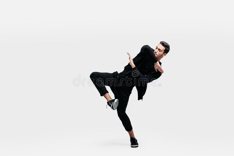 De modieuze jonge mens die een zwart sweatshirt en een zwarte broek dragen maakt gestileerde bewegingen van heup -heup-poh stock foto's