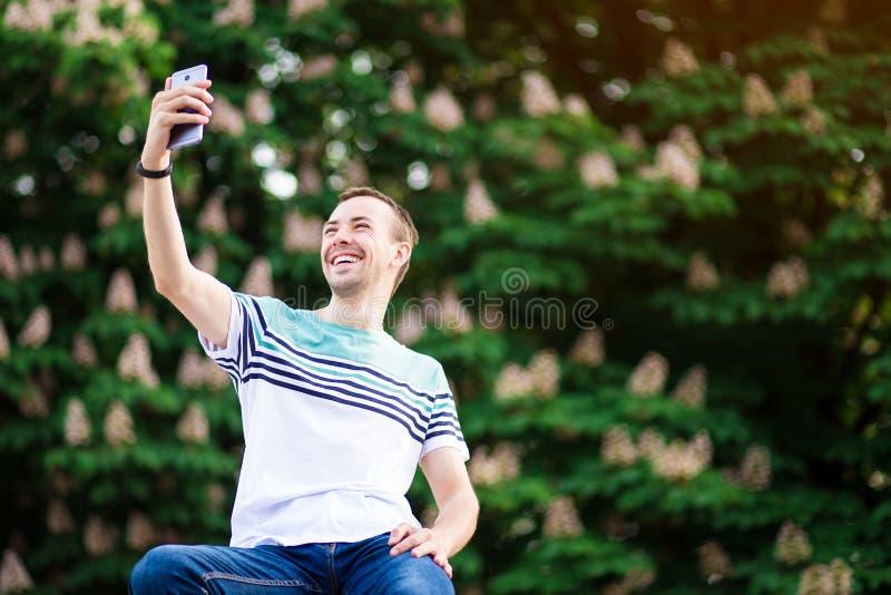 De modieuze jonge mens die van Parijs een selfie met smartphone in openlucht in park op zonnige de zomerdag nemen stock foto
