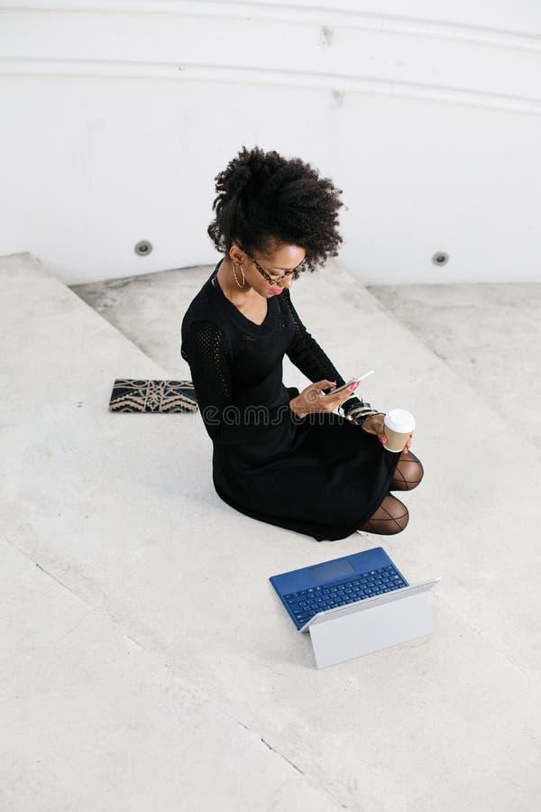 De modieuze jonge professionele vrouw die van het afrohaar smartphone en tablet gebruiken stock foto's