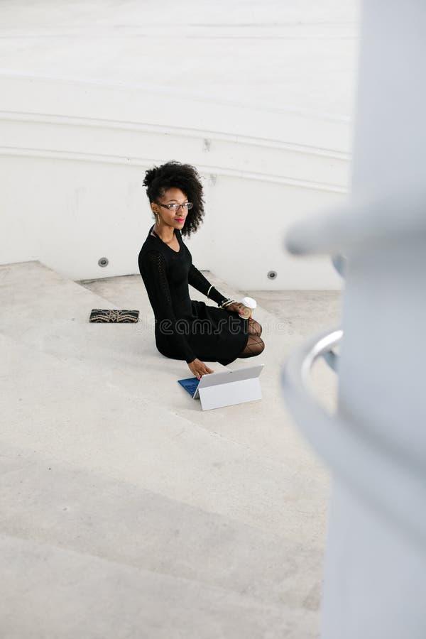 De modieuze jonge professionele vrouw die van het afrohaar tablet gebruiken stock afbeeldingen