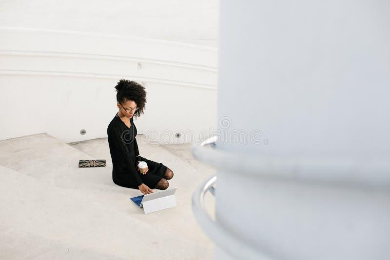 De modieuze jonge professionele vrouw die van het afrohaar tablet gebruiken stock foto