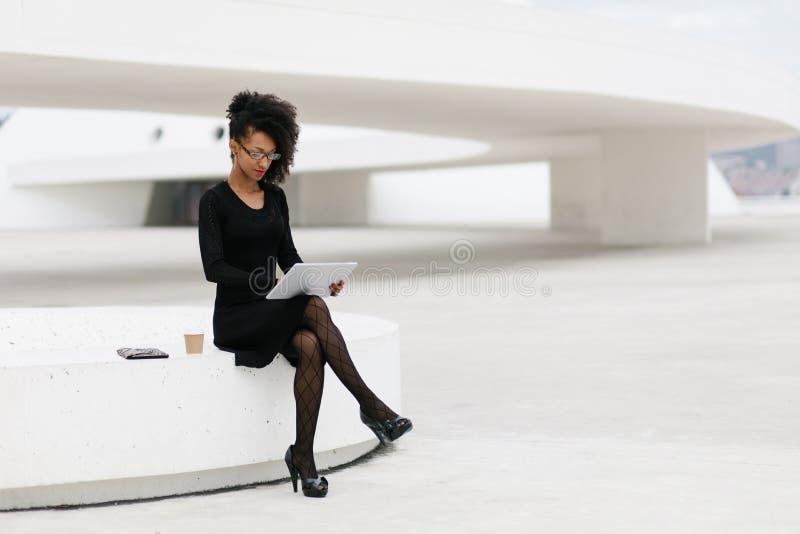 De modieuze jonge professionele vrouw die van het afrokapsel tablet gebruiken royalty-vrije stock afbeelding