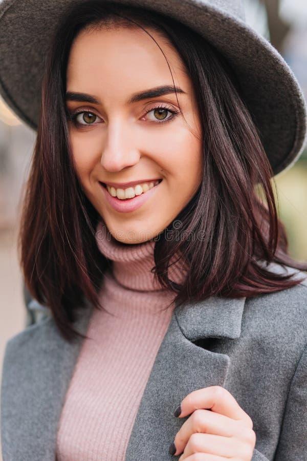 De modieuze jonge vrouw die van het close-upportret vrij met donkerbruin haar op straat lopen Grijze hoed, laag, luxekleren stock fotografie