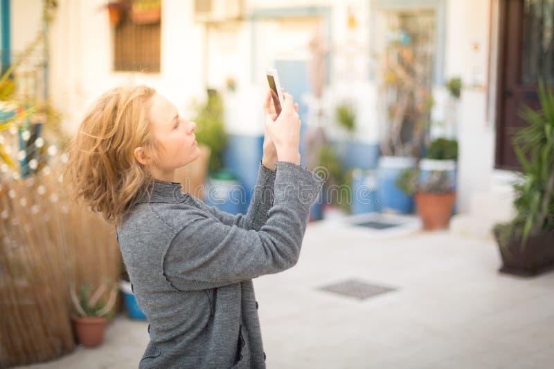 De modieuze jonge vrouw in een grijze laag buiten het huis maakt foto's van de stad stock fotografie