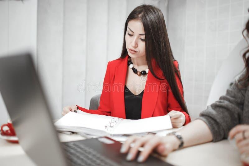 De modieuze jonge vrouwenontwerper werkt bij het ontwerpproject van binnenlandse zitting bij het bureau met laptop en stock afbeeldingen
