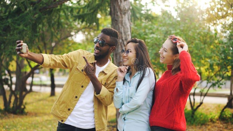De modieuze de jongerenman en vrouwen nemen selfie het dragen van zonnebril die en holdingssmartphone stellen glimlachen tijdens royalty-vrije stock foto