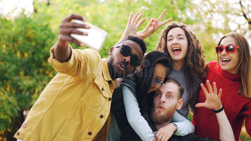 De modieuze de jongerenmeisjes en kerels gebruiken smartphone om selfie in park het stellen voor camera en het lachen te nemen st stock afbeeldingen