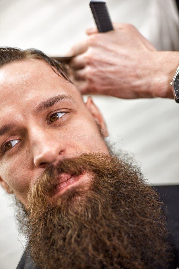 De modieuze kapper snijdt een brutale mens met een dikke baard royalty-vrije stock afbeelding